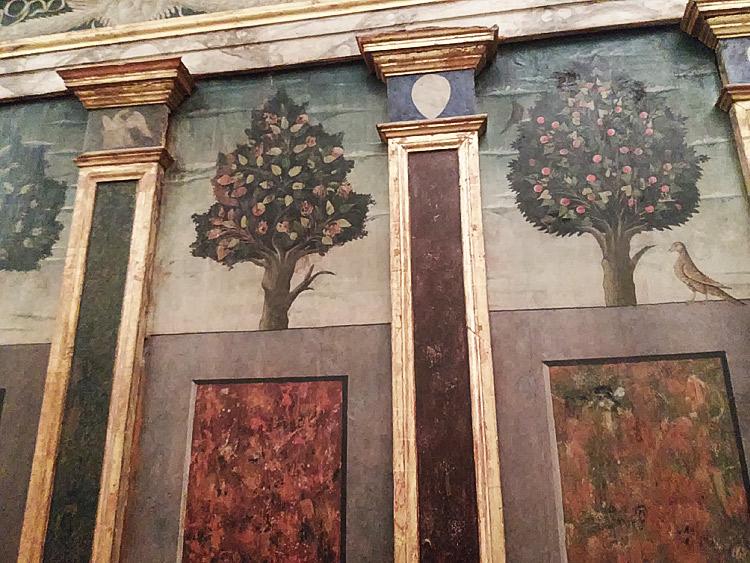 Particolare della parete con gli alberi e gli uccellini e, nei capitelli delle lesene, a sinistra l'aquila e a destra lo stemma dei Montefeltro