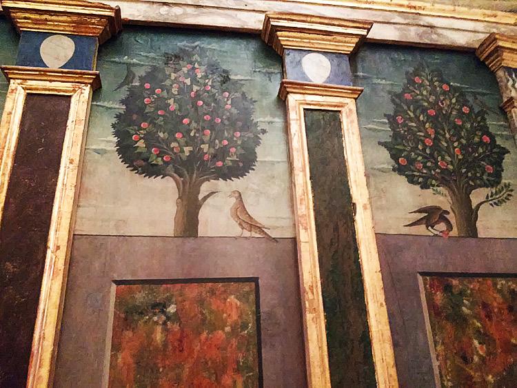 Particolare della parete con gli alberi e gli uccellini e, nei capitelli delle lesene, gli stemmi dei Montefeltro