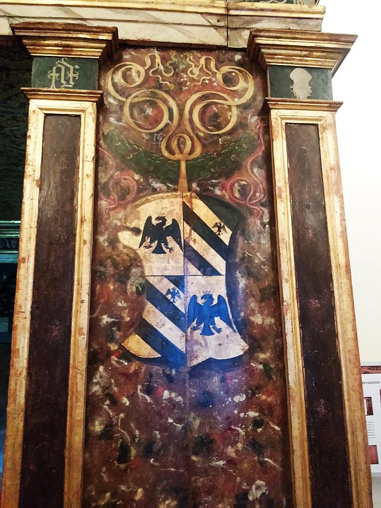Particolare dell'ingresso: si notino lo stemma feltresco appeso alla ghirlanda e, sulle lesene, a sinistra la sigla FF e a destra l'impresa della granata