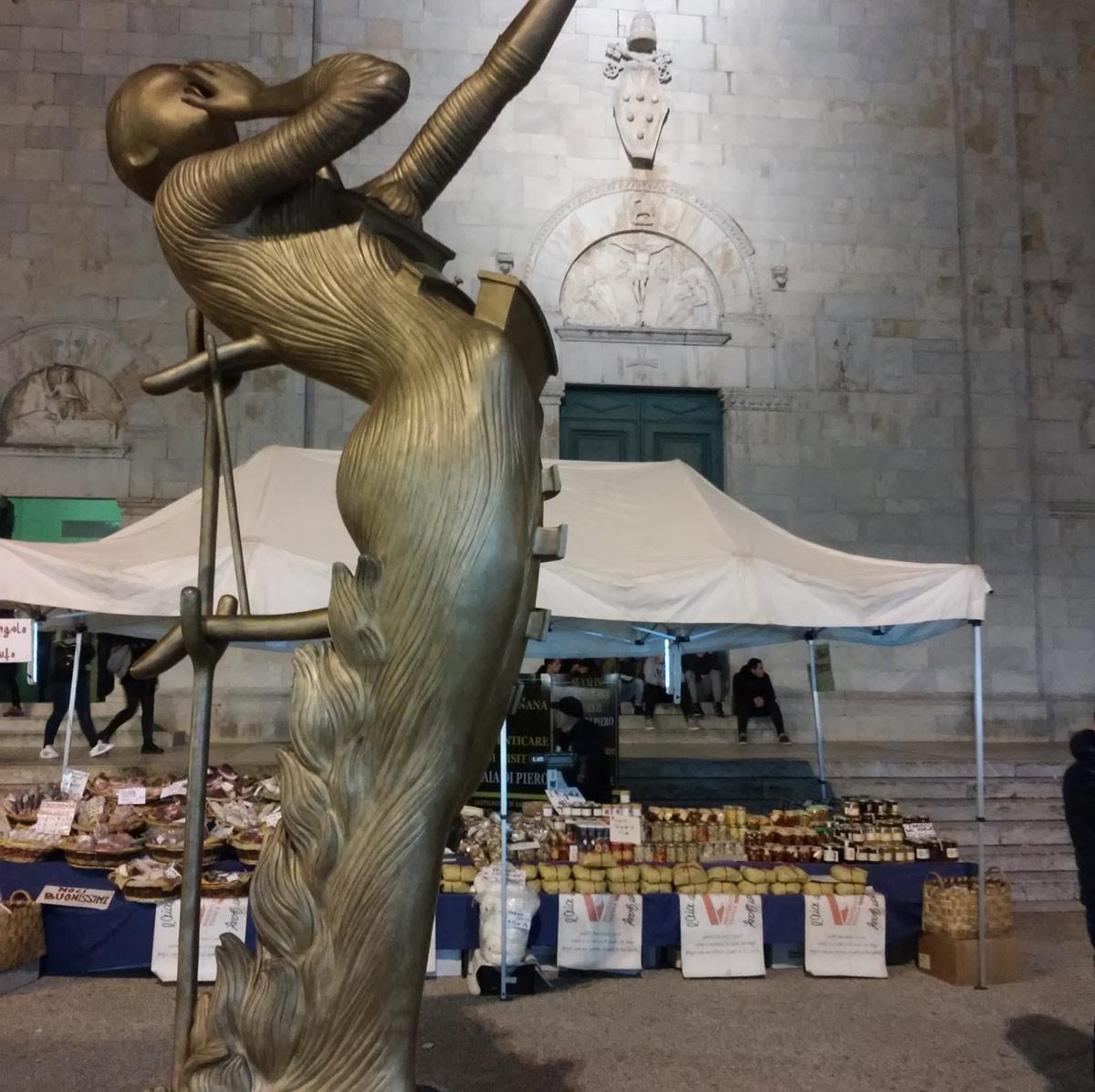 Una delle sculture in piazza del Duomo sullo sfondo di salumi e caciotte