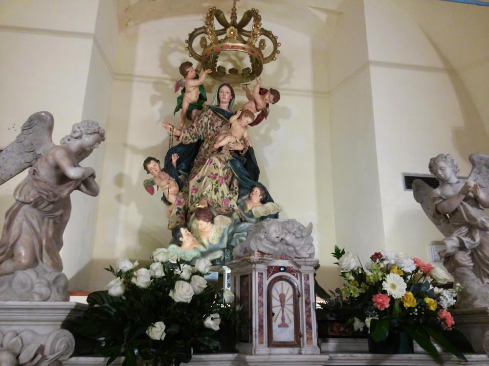 La Madonna del Rosario dietro gli angeli dell'altare
