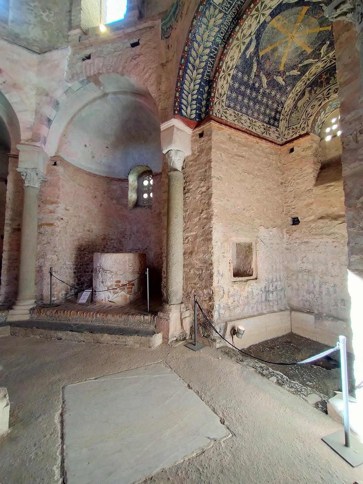 La nicchia con la decorazione musiva e quella con il fonte battesimale cilindrico e in muratura