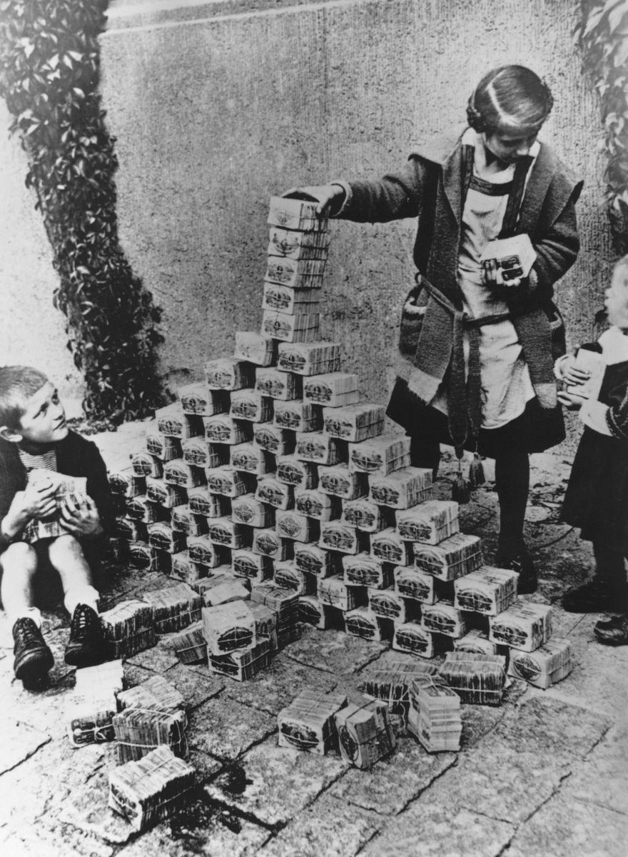 Germania, 1923: bambini che fanno castelli di carta con mazzette di banconote